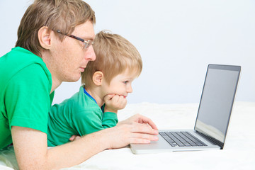 father and son looking at laptop at home
