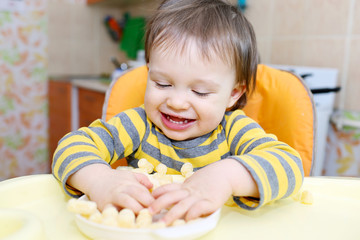 happy baby playing with corn curls