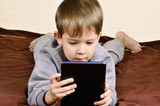little boy 5 years lying and playing on a tablet