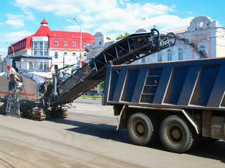 Cold planer machine loading milled asphalt into truck