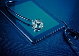 medical stethoscope on modern digital tablet on wood table