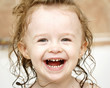 Laughing little girl having fun in the bath