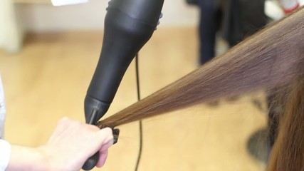 Footage of barber dries hair of model