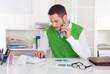 Kaufmann sitzend im Büro kalkuliert die Kosten