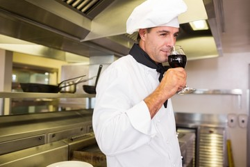 Male cook drinking red wine in kitchen
