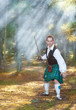 Handsome scottish man with sword  in the forest