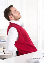 Mann mit Rückenschmerzen sitzend im Büro