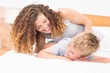 Happy mother tickling her son on bed
