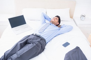 Smiling businessman lying on his bed