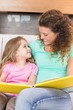 Happy mother sitting with her little daughter reading a storyboo