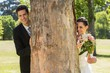 Happy newlywed couple behind tree trunk in park