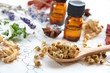 essential oils with dried herbs on science sheet