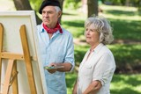 Woman watching mature man paint in park