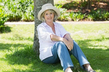 Mature woman sitting against a tree in park