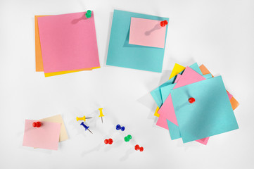 Blank colorful paper notes and colorful pins on white.
