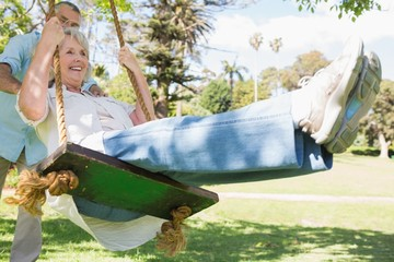 Mature couple at swing in the park