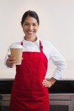 Happy young barista offering cup of coffee to go