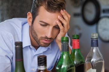 Drunk businessman looking at spirit bottles