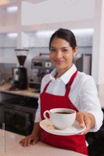 Pretty barista offering cup of coffee smiling at camera