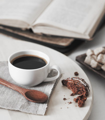 fresh coffee with cookie and book