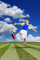 male football player and soccer ball floating on green grass of