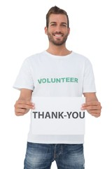 Smiling young male volunteer holding 'thank you' paper