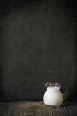 glass jug of milk on blackboard for text