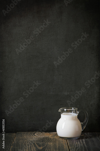 glass jug of milk on blackboard for text