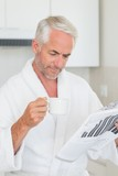 Happy man reading newspaper at breakfast in a bathrobe