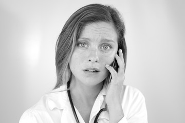 Shocked young woman doctor on the phone getting sad