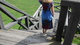 woman with blue flowered dress climbs the wide wooden stairs