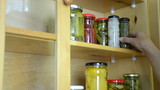hand puts cupboards shelves jars different canned vegetables