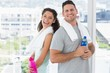 Couple with towels and water bottles at gym