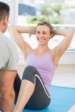 Trainer assisting woman in doing sits up