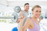 Woman and man lifting barbells
