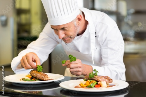 Leinwanddruck Bild Concentrated male chef garnishing food in kitchen