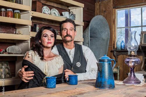 Deadpan Western Sheriff and Woman Pose Inside House