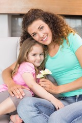 Smiling mother getting little flowers from her cute daughter