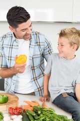 Smiling father showing his son a yellow pepper