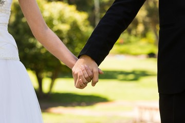 Mid section of newlywed couple holding hands in park
