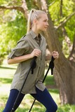 Beautiful young woman Nordic walking in park