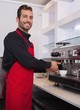 Cheerful young barista making cup of coffee