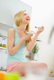 Smiling young woman eating muesli in kitchen