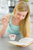 Young woman eating yogurt and reading book