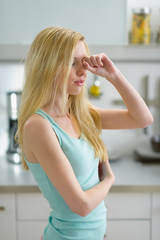 Young woman rubbing eyes after sleep in kitchen