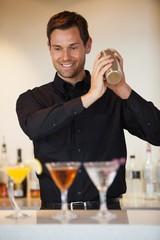 Happy bartender shaking cocktails