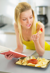Young woman eating chips and reading book