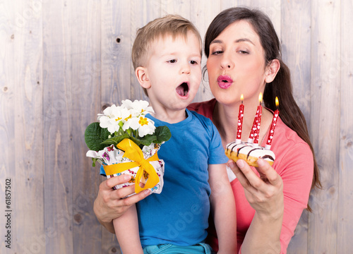 young boy celebrating mothers day with cake and candles