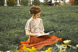 young beautiful girl with a book in the autumn park