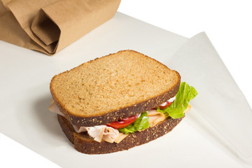 Turkey sandwich on wax paper with brown paper bag